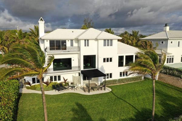 Drone view of large white home with black trim, front view, residential neighborhood, multiple double panel impact windows, FS-300 Maxi View Impact Storefront windows by Aldora, manicured lawn, palm trees, tropical environment