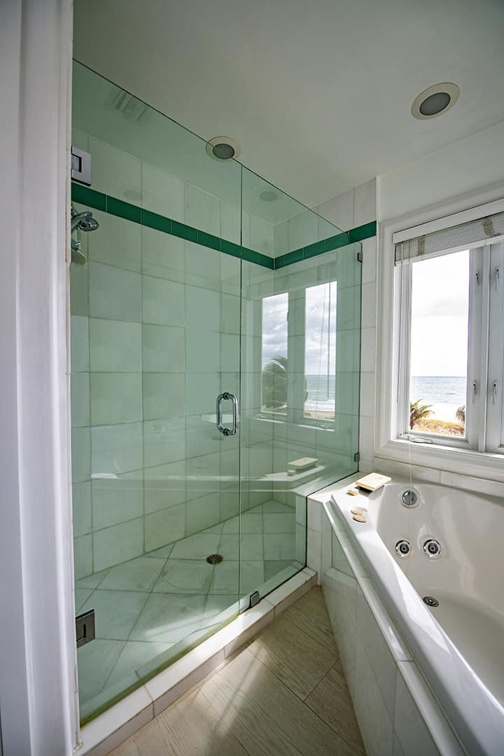 Glass shower door and glass shower wall by Aldora, walk-in shower, white ceramic tile wth green accents, chrome shower hardware, jet soaker tub to right of shower