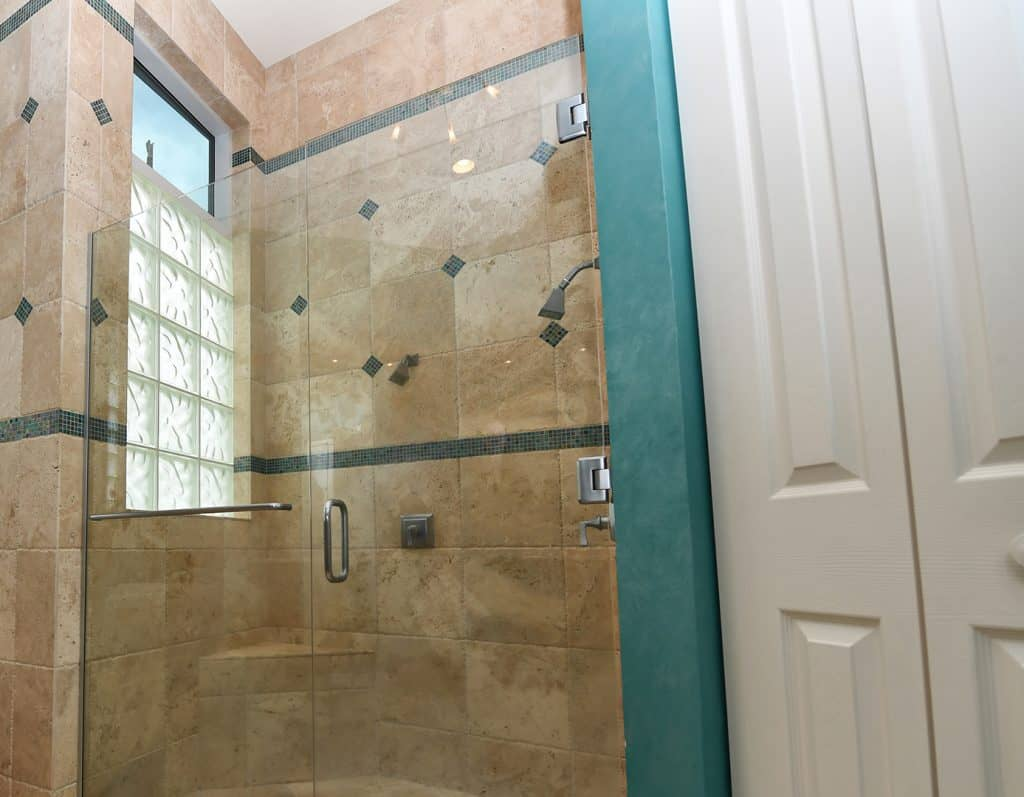 Floor view looking upward at master bathroom, beige ceramic tile with green accents, step up soaker tub, tiled glass window, accent candles, swinging glass door and glass shower wall by Aldora, chrome hardware