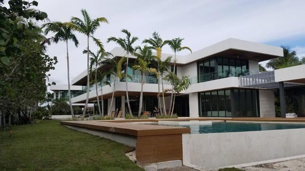 Two-story white home with glass impact walls, floor-to-ceiling windows on first and second floors with black trim, SMI-175 Impact Storefront system from Aldora, grey accent pillars, infinity pool in foreground with wood trim, palm trees, tropical landscaping