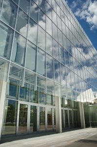 Angled view of multi-level glass commercial building with five sets of double outswinging K2-Summit Impact Doors by Aldora, curtain wall windows above and surrounding doors to create building walls, side walk in front of building