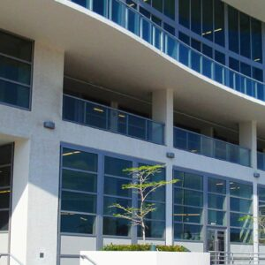 Commercial building entrance, grid SMI-175 impact storefront system windows and doors on multiple levels, curved architectural accents, minimal tropical landscaping in front of building