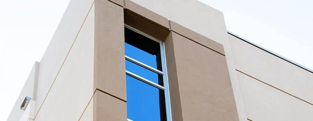 Aldora SMI-090 windows run down the corner of a commercial cement building