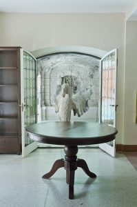 Internal entrance of arched glass double door with inlaid glass details, inward swinging glass door, round wood table in center of room, built in bookshelf on left