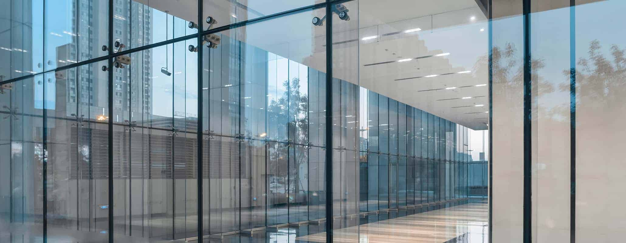 An empty room encased in Aldora all-glass entry doors looking out on a city sidewalk.