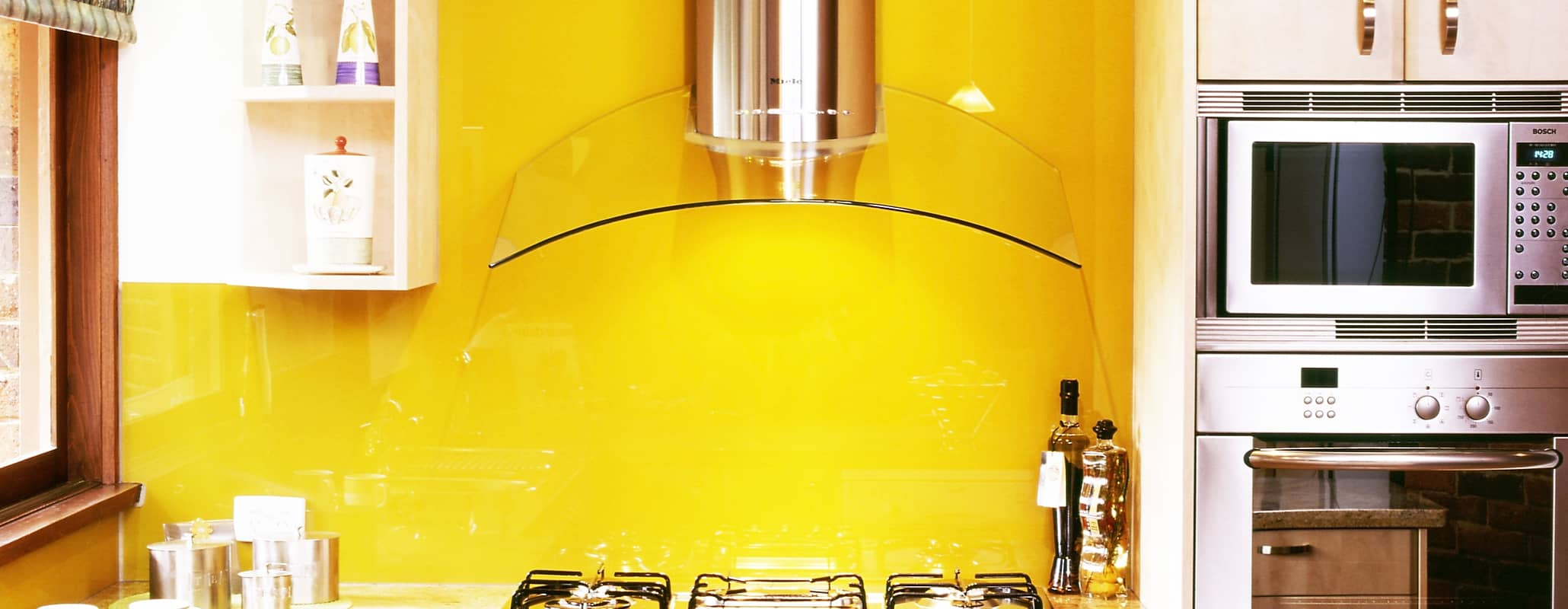 Kitchen view with microwave and oven on the right, surrounded by cabinets. Stove in front of yellow Aldora back-painted glass and underneath glass and metal hood. Sink to the left with open cabinets showing cups.