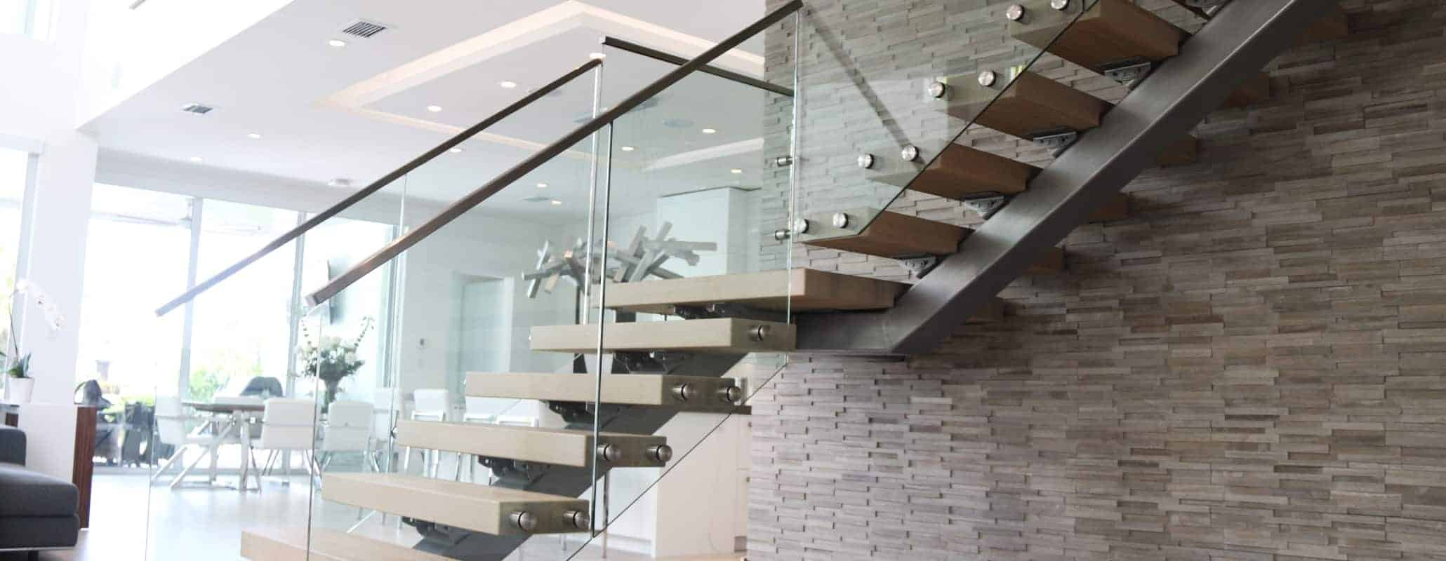 Staircase with glass railings in a residential setting with kitchen and living room in background.
