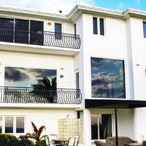 Ground view looking up at expensive residential home, front set system glass windows by Aldora, impact glass, sliding glass doors with balconies, manicured lawn, palm trees