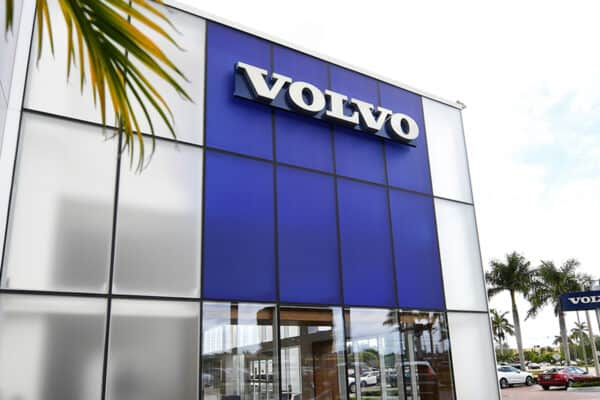 External view of Volvo car dealership, curtain wall glass with aluminum framing by Aldora, blue tinted glass on second level, front set system, manicured landscaping, parking lot and palm trees in background.