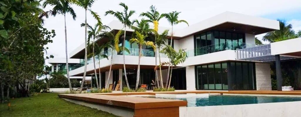 Two-story white home with glass impact walls, floor-to-ceiling insulated Aldora windows on first and second floors with black trim, SMI-175 Impact Storefront system from Aldora, grey accent pillars, infinity pool in foreground with wood trim, palm trees, tropical landscaping